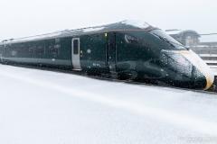 Class 801 Super Express Hitachi train departs Penzance station during heavy snow blizzard